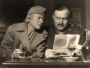 Janet Flanner and Ernest Hemingway, both in uniform, seated reading papers at a table in the Deux Magots cafe in Paris, France
