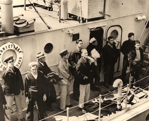 USS Squalus (SS-192) Rescue Operations, May 1939 Squalus' Commanding Officer, Lieutenant Oliver F. Naquin (center, hatless, wearing khaki pants), with other survivors on board the Coast Guard Cutter Harriet Lane, bound for the Portsmouth Navy Yard, Kittery, Maine, following their rescue, 25 May 1939.