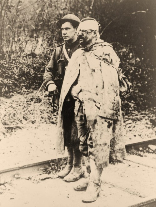 An orderly escorting a wounded, captured soldier to a field hospital for treatment.