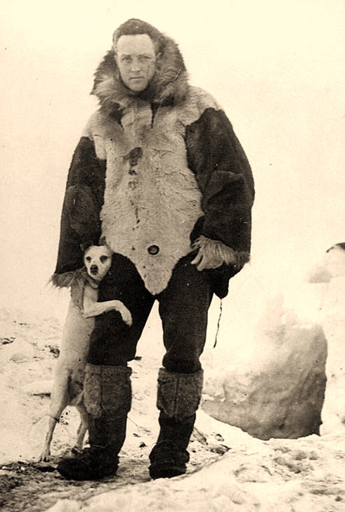 "Commander Richard E. Byrd, USN Dressed in furs, with his dog ""Igloo"", outside a hut during his first Antarctic Expedition, 12 April 1930. Official U.S. Navy Photograph, National Archives collection"