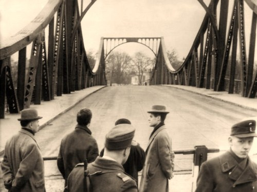 """Two groups of men huddled in trench coats and slouch hats meeting on a bridge. The man leading the first group is named """"Abel""""; the man leading the second is named """"Powers."""" Francis Gary Powers was an American pilot flying a Lockheed U-2 reconnaissance plane over the Soviet Union when he was shot down in May 1960. He was subsequently convicted of espionage and sentenced to 10 years in prison. Abel was a Soviet intelligence officer who had been found guilty of espionage in 1957. The """"U-2 incident"""" brought to an abrupt end President Eisenhower's efforts to implement an arms control agreement with the Russians and marked the end of the brief period of detente that had characterized the last years of the 1950s. The subsequent exchange of Powers for Abel on the Glienicker Bridge at the border between the U.S. sector of West Berlin and Potsdam, East Germany did little to improve relations between the two superpowers."""