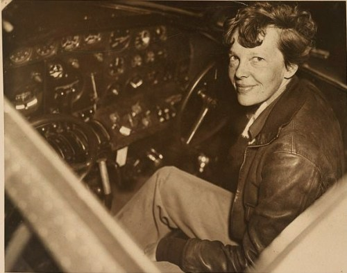 Photograph showing Amelia Earhart sitting in the cockpit of an Electra airplane.