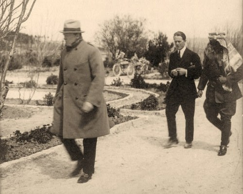 "Winston Churchill, ""Lawrence of Arabia,"" and Emir Abdullah walking in the gardens of the Government House, Jerusalem, during secret conference"