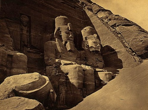 View of colossal figure,  probably Ramses II, carved into rock that  is the Great Temple at Abu Sunbul, Egypt