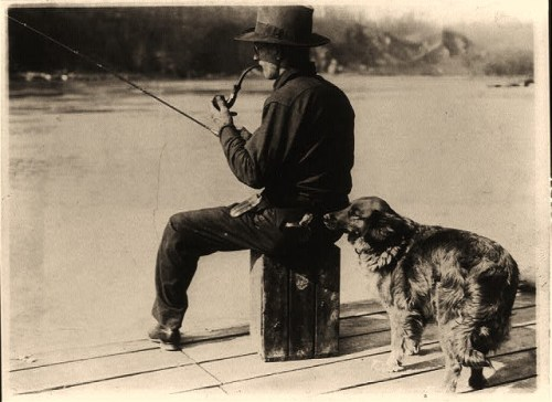 Hooch Hound, a dog trained to detect liquor (as suggested to Commissioner Haynes by a prohibition agent in Colorado), sniffs at flask in back pocket of man, seated, fishing on pier on the Potomac River