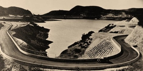 Photograph shows a bird's-eye view of a large reservoir with mountains in the background and highway in the foreground, in Los Angeles, California.