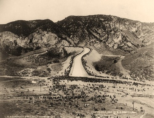 Illustration showing bird's-eye view of mountainside, tunnel opening, canal forming Owensmouth Cascase, and crowd celebrating the opening of the gates releasing water from the Owens River into San Fernando Valley via canal.