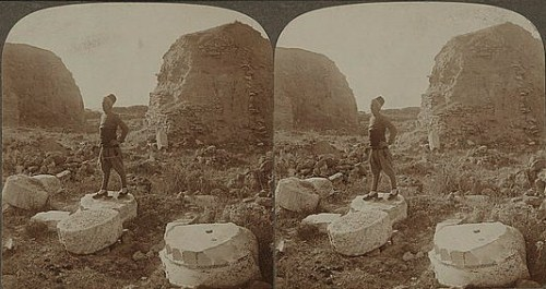 Stereograph showing man standing on column slabs in front of two mounds. Storied remnants of one time magnificence - centre of ancient Troy.