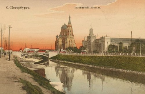 Print shows the Warsaw railway station and Church of the Resurrection of Christ along the Obvodny Canal in St. Petersburg, Russia.