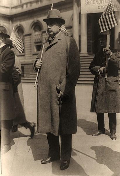 John Pierpont Morgan, Jr., full-length portrait, standing, facing left, holding U.S. flag