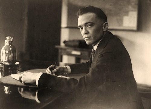 J. Edgar Hoover, half-length portrait, facing left, seated at desk, holding pen