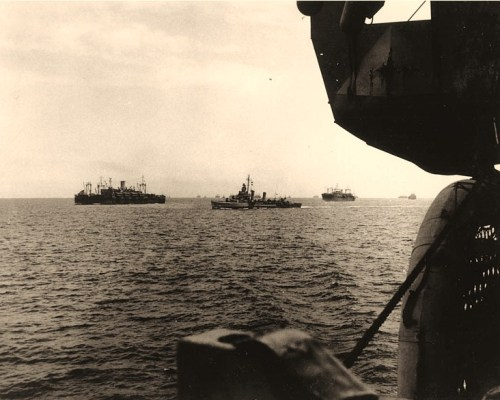 "Sicily Invasion, July 1943 Task Force 85 (""Cent"" Force) en route to the landings at Scoglitti, Sicily, on 8 July 1943. Photographed from its flagship, USS Ancon (AGC-4). USS Leonard Wood (APA-12) is at left. The next transport astern of her is USS James O'Hara (APA-90). The destroyer in the center is not identified; USS Parker (DD-604), Kendrick (DD-612), Laub (DD-613), Mackenzie (DD-614), Cowie (DD-632), Doran (DD-634), and Earle (DD-635) were assigned to this force. Official U.S. Navy Photograph, now in the collections of the National Archives."
