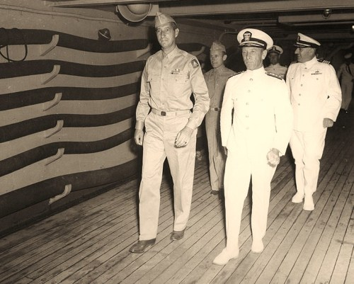 Lieutenant General Mark W. Clark, U.S. Army (left), Commanding General, Fifth Army, and Rear Admiral Alan G. Kirk, USN, Commander Task Force 85 On board USS Ancon (AGC-4) during the Sicily operation, July 1943. In the right background is Captain Paul L. Mather, USN, Ancon's Commanding Officer. Official U.S. Navy Photograph, now in the collections of the National Archives.
