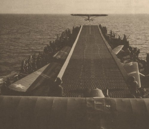 "An Army Piper L-4 Cub artillery observation plane takes off from an LST at Anzio, 1944. LST-386 had an improvised ""flight deck"" installed in 1943 and flew off four such planes during the landing on Sicily. Later LST modifications, like this one, could carry up to 10 planes and supported the Anzio landing and the invasion of southern France. During 1944, LST-776 evaluated an experimental catapult for launching light planes, as well as Brodie gear. In this system, a cable was stretched between booms to one side of the ship, and planes were launched from a quick-release trolley. LST-776 operated Marine OY-1's over Iwo Jima and Army L-4's at Okinawa."