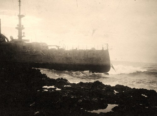 USS Memphis (Armored Cruiser # 10) Wrecked at Santo Domingo, Dominican Republic, where she was thrown ashore by tidal waves on the afternoon of 29 August 1916. This view probably was taken early on 30 August, as the ship appears to be abandoned. Note the U.S. Ensign hanging from the ship's stern where the flagstaff had broken away. The top of her rudder and propeller is also visible. Photographed by the local U.S. Consul, Carl M.J. von Zeilinski. U.S. Naval Historical Center Photograph.