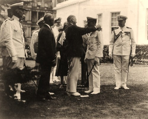Commander Claud A. Jones, USN Receives the Medal of Honor from President Herbert Hoover, in ceremonies at the White House, 1 August 1932. Cdr. Jones' wife and son are partially visible behind him and the President. Captain Walter N. Vernou, Presidential Naval Aide, is at right. In the left center is Secretary of the Navy Charles Francis Adams. At the extreme left are Rear Admiral Samuel M. Robinson, Chief of the Bureau of Engineering; Captain Harold G. Bowen, Assistant Chief of the Bureau of Engineering (partially visible); and Captain Harold Stark, Aide to the Secretary of the Navy (partially visible). Commander Jones received the Medal for heroism on board USS Memphis (Armored Cruiser # 10) when she was wrecked on 29 August 1916. U.S. Naval Historical Center Photograph.