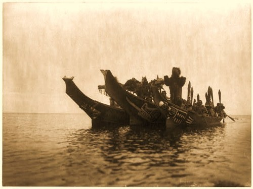 During the winter ceremony, Kwakiutl dancers in masks and costumes representing (l to r) Wasp, Thunderbird, and Grizzly-bear, arrive in canoes. Edward S. Curtis - Published in: The North American Indian