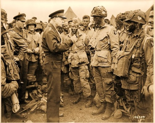 "Photo shows General Eisenhower talking with American paratroopers on the evening of June 5, 1944, as they prepared for the Battle of Normandy. The men are part of Company E, 502nd Parachute Infantry Regiment, at the 101st Airborne Division's camp in Greenham Common, England. Photo includes Sgt. Russell Wilmarth, behind Eisenhower's chin (Source: Alan Offen, 2009); Lt. Wallace C. Strobel with a ""23"" tag (Source: ""Dwight David Eisenhower: The Centennial, CMH Pub 71-40); Ralph ""Bud"" Thomas, to the left of Strobel (Source: Eileen Thomas Hayes, 2012); and probably Corporal Donald E. Kruger, in front row, far right, wearing a musette bag on his chest"