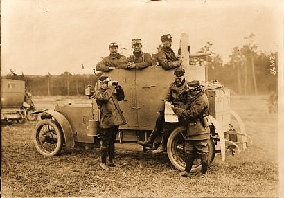 Soldiers looking at map by armored car probably in France