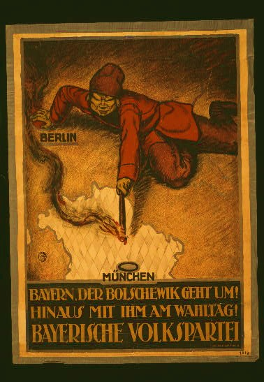 Poster shows a Bolshevik leaning on a map of Europe and setting fire to Bavaria. Text: The Bolshevik is coming! Throw him out on Election Day! Bavarian People's Party.