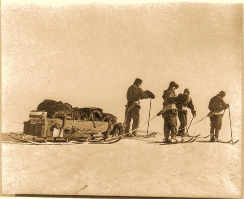 Photograph show expedition members Capt. Lawrence Oates, Lt. Henry Robertson Bowers, Capt. Robert F. Scott, Dr. Edward A. Wilson, and P.O. Edgar Evans on skis, towing a sled of provisions.