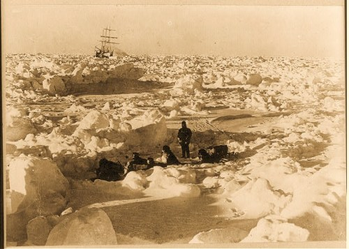 Photograph shows crew member with dog team hitched together sitting among ice floe; in the far background the Endurace is stuck.