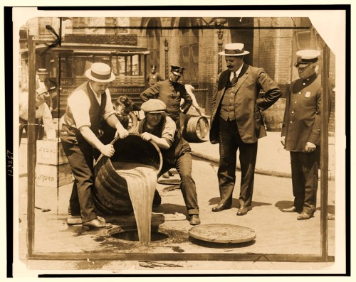 New York City Deputy Police Commissioner watching agents pour liquor into sewer following a raid during the height of prohibition.
