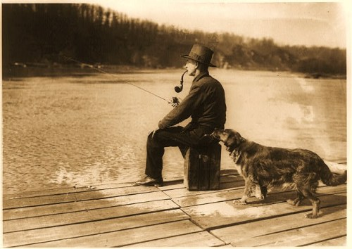 "The ""Hooch hound"" in action. Man seated on pier, with pipe in his mouth, fishing on the River, as dog trained to detect liquor takes a bottle from his back pocket."