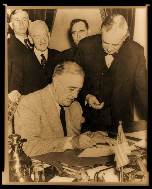 President Franklin D. Roosevelt signing the declaration of war as Sen. Tom Connally holds the watch to fix the exact time