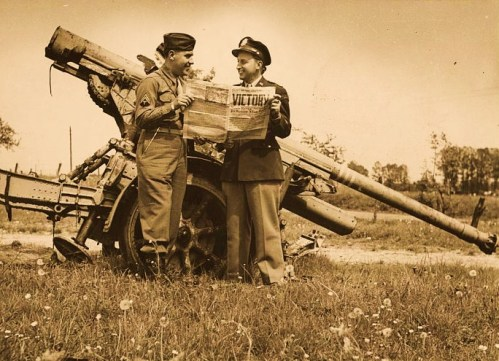 William R. Wilson (right) and brother Cpl. Jack Wilson (left) standing by a German 88 mm gun at Verdun, France on VE Day